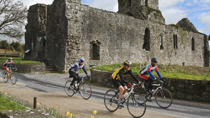 Cycling group passing ruined church, Limerick