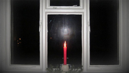The Christmas candle in the window on Christmas Eve